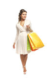 A young woman in a dress holding shopping bags Stock Photos