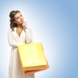 A young woman in a dress holding shopping bags Stock Photography