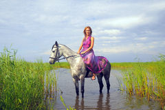 Young woman in a dress on a horse Royalty Free Stock Photos