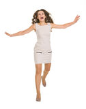 Young woman in dress jumping forward Royalty Free Stock Photo