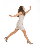 Young woman in dress jumping. Side view Stock Images