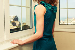 Young woman in dress looking out the window Royalty Free Stock Photos