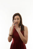 Young woman in dress. Woman making a call on a mobile phone looking a bit shocked and surprised about something with her hand up to her mouth royalty free stock photography