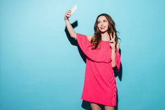 Young woman in dress making selfie and showing peace gesture Stock Photos