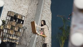 A young woman in dress paints a painting on a canvas, standing behind an easel, in an atmospheric workshop . Art academy. Or drawing school. Inspiration. Talent stock footage