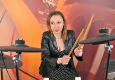 Young woman in dress with polka dots and jacket playing drums Stock Image