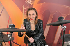 Young woman in dress with polka dots and jacket playing drums Royalty Free Stock Images
