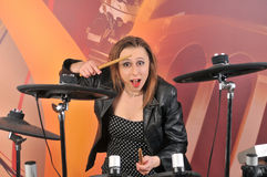 Young woman in dress with polka dots and jacket playing drums Royalty Free Stock Image