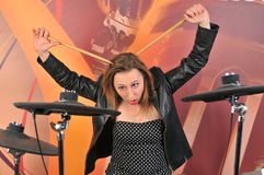 Young woman in dress with polka dots and jacket playing drums Stock Photography