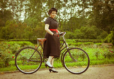 Young woman in dress posing with retro bicycle in the park. Stock Image