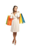 A young woman in a dress posing with shopping bags Royalty Free Stock Photo