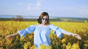 Young woman in dress rejoices, spinning around in rapeseed yellow flowers field. Freedom, love, nature concept. Young woman in dress rejoices, spinning around stock video