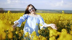 Young woman in dress rejoices, spinning around in rapeseed yellow flowers field. Freedom, love, nature concept. Young woman in dress rejoices, spinning around stock video footage