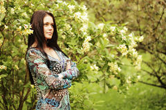 Young woman in dress relaxing in  garden Stock Images