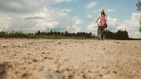 A young woman in a dress rides a bicycle on the background of a field in the village. stock video footage