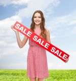 Young woman in dress with sale sign Stock Photo