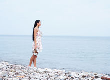 A young woman in a dress on a sea background Stock Image