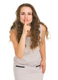 Young woman in dress showing shh.. gesture Stock Photography