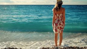 Young woman in dress standing on a beach at sunset over the sea. stock footage