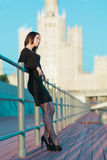 Young woman in dress standing leaning on railing Royalty Free Stock Photo