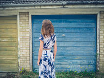 Young woman in dress standing outside garage Royalty Free Stock Image