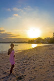 Young woman in dress standing on sand at sunset Stock Photography