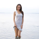 A young woman in a dress is standing in the water royalty free stock photography