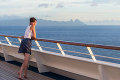 Young woman in dress stands on the deck of cruise liner Stock Photos