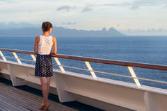 Young woman in dress stands on the deck of cruise liner and look Royalty Free Stock Image