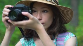 Young woman in dress and straw hat takes pictures of nature with retro camera stock video