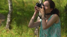 Young woman in dress and straw hat takes pictures of nature with retro camera stock footage