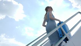 Young woman in dress with travel suitcase rises by staircase at airport. Young woman passenger in dress with travel suitcase rises by staircase at airport on stock video footage