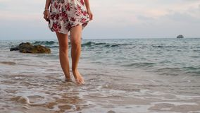 Young woman in dress walking on beach stock video