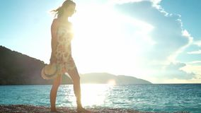 Young woman in dress walking on a beach at sunset stock footage