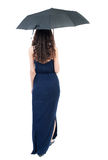 Young woman in dress walking under an umbrella. Royalty Free Stock Photos