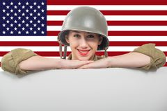 Young woman dressed in American ww2 military uniform showing empty blank signboard stock photo