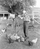 Young woman dressed as a farmer bringing food to the chicken Royalty Free Stock Photo