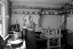 Young woman dressed as pilgrim in typical kitchen,Old Sturbridge Village,Mass,2014 Stock Photography