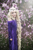 Young woman dressed as Rapunzel in purple gown Stock Photo