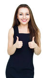 Young woman dressed in black dress showing thumb up gesture over white. Young woman dressed in black dress showing thumb up gesture using both hands, isolated Royalty Free Stock Photo