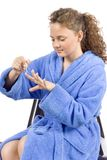 Young woman dressed blue bathrobe painting nails Royalty Free Stock Image