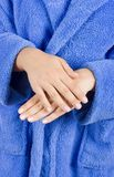 Young woman dressed blue bathrobe rubbing cream Stock Photos