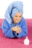 Young woman dressed blue bathrobe rubbing cream into her hands. On the pink carpet stock photography