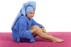 Young woman dressed blue bathrobe rubbing cream into her leg Stock Image