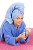 Young woman dressed blue bathrobe and towel filing nails. On the pink carpet Royalty Free Stock Photography