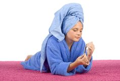 Young woman dressed blue bathrobe and towel filing nails Stock Photo