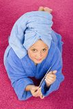 Young woman dressed blue bathrobe and towel filing nails. On the pink carpet royalty free stock photo