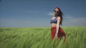 Young woman dressed in Boho style swaying in the middle of green wheat field is catching wind blowing Close her eyes to. Sun stock video footage