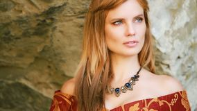 A young woman dressed in a dark orange medieval dress stock video