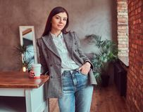 Young woman dressed in a gray elegant jacket holding cup of takeaway coffee while leaning on a table in a room with loft. Portrait of a young woman dressed in a stock image